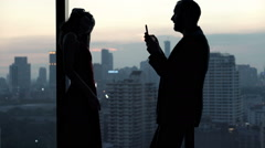 Young man taking photo of his pretty girlfriend standing close to the window dur Stock Footage