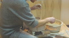 Man is Rotating a Pottery Wheel Molding a Clay Pot Attentively with Spatula Stock Footage