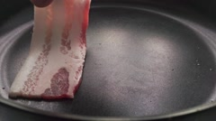 Close up video of two frying bacon slices Stock Footage