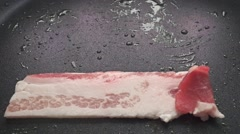 Close up video of two horizontal frying bacon slices Stock Footage