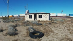 Abandoned Shack In Desert With Moving Freight Train Behind Stock Footage