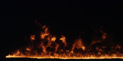 A fire half-hidden behind oily black smoke gathers strength and touches the top Stock Footage