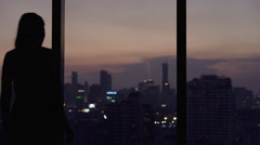 Young woman looking at cityscape at night Stock Footage