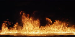 Flames rise across the frame from a pool of liquid fuel Stock Footage