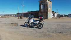 Dual Purpose Motorcycle At Abandoned Gas Station In Desert Stock Footage