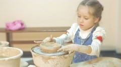 Kid is Rotating a Pottery Wheel by Hand Molding an Edges of Clay Circle Stock Footage