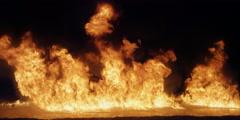Flames burning on a lake of liquid fuel gradually subside Stock Footage