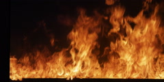A blaze grows in intensity until the tops of the flames disappear above the - stock footage