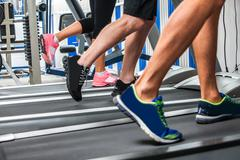 Group of legs wearing sneakers running on treadmill Stock Photos