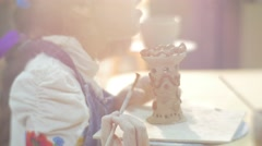 Little Girl is Smiling And Glazing a Clay Figurine Tower Painting with Brush Stock Footage