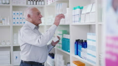 4K Senior man customer browsing the products in a chemist shop Stock Footage