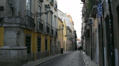 People walk in old narrow city alley, Lisbon, Portugal - stock footage