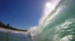 Green surfing wave breaking on beach POV Stock Footage