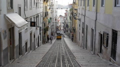 Yellow tram and people go up a steep narrow street, Lisbon, Portugal Stock Footage