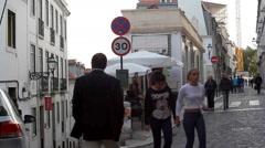 People walk in narrow steep winding streets of Lisbon, Porugal Stock Footage