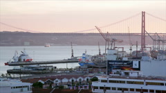 25 de Abril Bridge, sunset, boats in harbor, Lisbon, Portugal Stock Footage