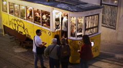 Tourists board full yellow tram cart at night, Lisbon old city, Portugal Stock Footage