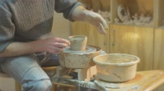 Man Puts The Hand Into a Bowl of Water Molding Clay Pot Attentively with Stock Footage