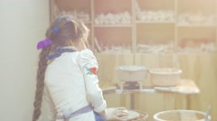 Girl is Molding a Clay Circle Kid's Back Child Rotating a Pottery Wheel Little Stock Footage