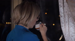 Adult woman sips a cup of coffee after dinner, city lights Stock Footage