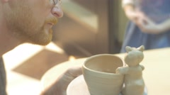 Man is Working With Clay Blurred Kid is Walking Covering a Clay Pot and Cat Stock Footage