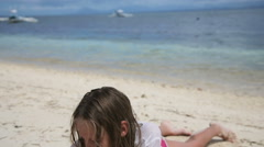 Happy child playing with sand on beach in summer. Stock Footage