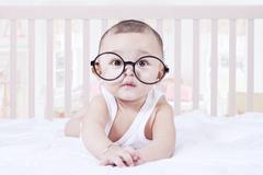 Stock Photo of Cute baby wearing glasses in bedroom
