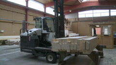 Industrial carpentry forklift truck lifting wooden beams Stock Footage