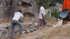 Indian worker breaks large stones with a sledgehammer Stock Footage