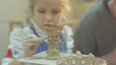 Kid With Her Face Concentrated Is Glazing a Clay Figurine Attentively with Her Stock Footage