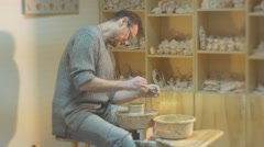 Man is Rotating a Pottery Wheel Eagerly Molding Clay Pot Attentively Man is - stock footage
