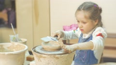 Kid is Molding an Edges a Vase With Spatula Child Little Blonde Girl is Working Stock Footage