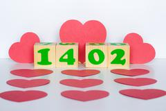 Wood cube with inscription 14 february and red hearts shape - stock photo