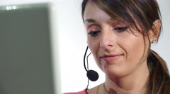 Attractive brunette listen to earphone and types on the laptop Stock Footage