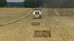 Hay baler producing rectangular straw bales from rye straw Stock Footage