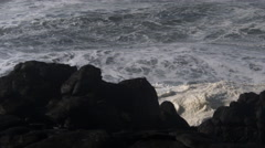 Foaming waves rise to smother a dark foreground cliff, spray spouts from a - stock footage