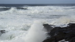 Foaming waves batter dark rocks, flinging towering billows of foam toward the Stock Footage