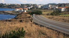 A man walking up the hill road and cars passing on the road in Jeju island Stock Footage