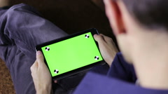 Man Using Tablet Computer on the Couch  with Green Screen Stock Footage