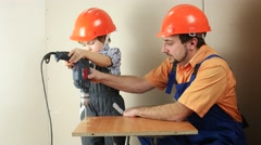 Father and son with one drill make hole Stock Footage