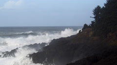 A rocky sea cliff battered by crashing breakers - stock footage