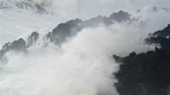Towering white waves crashing over ridges of black lava Stock Footage