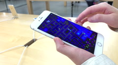 Woman playing game on iphone inside Apple store - stock footage