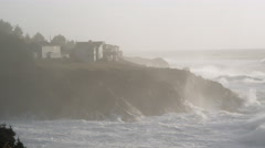 Seen through blowing mist, powerful waves assail a cliff below coastal homes Stock Footage