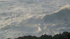 Foaming waves toss below dark rocks as the next breaker comes crashing in Stock Footage