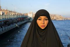 Stock Photo of Woman dressed with black headscarf, chador on istanbul street, turkey