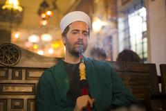 islamic man with traditional dress smoking shisha, drinking tea. - stock photo