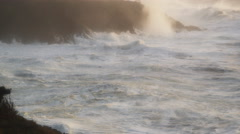 Powerful foaming waves crash into a rocky cove along a storm-battered shore Stock Footage