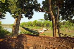 tourist girl sleeping on hammock, luang prabang, laos. - stock photo