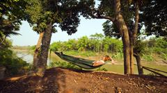 Stock Photo of tourist girl sleeping on hammock, luang prabang, laos.